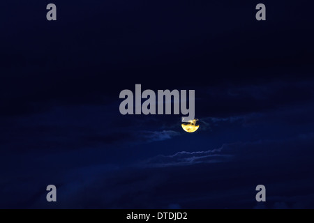 Full yellow moon in a deep blue cloudy night sky - Stock Photo