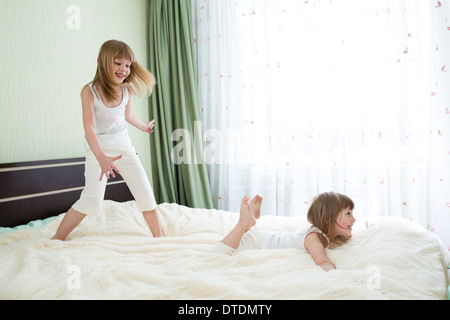 Two sisters playing on bed together - Stock Photo
