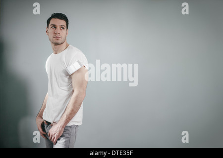 Part of series showing different ways one carries a smartphone, folded in t-shirt sleeve oldschool style. - Stock Photo