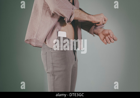 Part of series showing different ways one carries a smartphone, tucked in waist of tight jeans. - Stock Photo