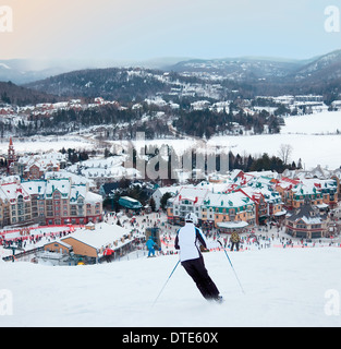 Mont-Tremblant, Canada - February 9, 2014: Skiers and snowboarders are sliding down the main slope at Mont-Tremblant. - Stock Photo
