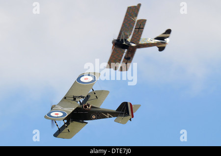 Two replica aircraft dogfight as if over the trenches of World War I - the Great War. One German, one British Royal - Stock Photo