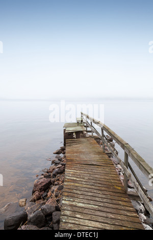 Old ruined wooden pier on Saimaa lake in foggy morning - Stock Photo
