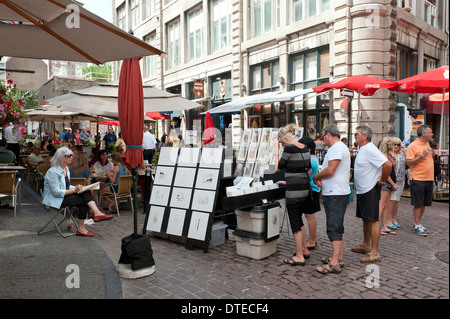 Visitors looking at prints put up for sale by an artist in Old Montreal, province of Quebec, Canada. - Stock Photo