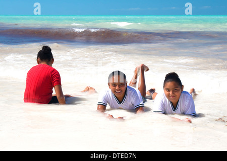 Mexican girls in their school uniforms enjoying the warm waters of Isla Holbox,  state of Quintana Roo. - Stock Photo