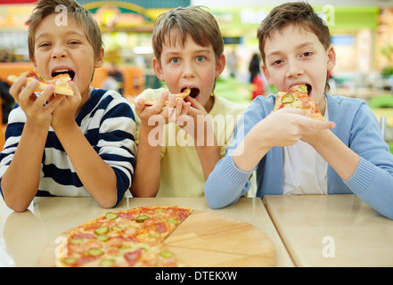 Three little boys eating pizza at cafe - Stock Photo