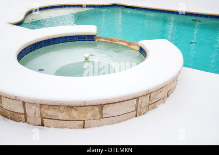 Outdoor hot tub or spa by swimming pool surrounded by snow in the winter - Stock Photo