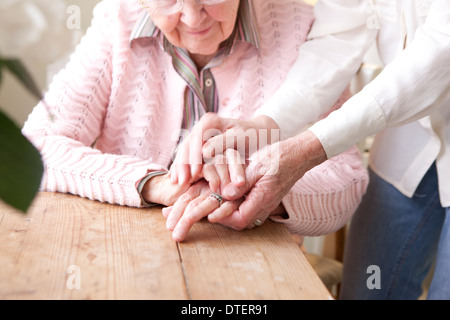 Close-up of hands of mature woman holding hands of elderly woman