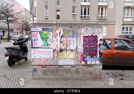 Layers of bill posters stuck onto street housing beginning to peel off and show signs of wear on cobbled street - Stock Photo