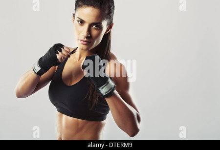 Pretty young woman wearing boxing gloves posing in combat stance looking at camera. Fit young female boxer ready - Stock Photo