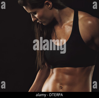 Image of fitness woman in sports clothing working out on black background. Young female with perfect muscular body. - Stock Photo