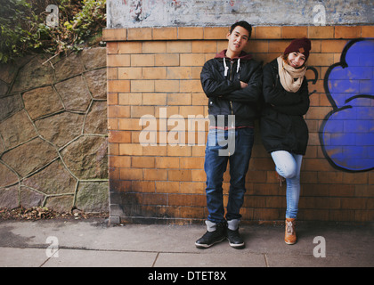 Beautiful young man and woman in warm clothes standing together leaning on a wall outdoors. Teenage Asian couple - Stock Photo