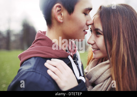 Close up image of cute young couple in love together in park. Asian teenage couple spending romantic time with each - Stock Photo