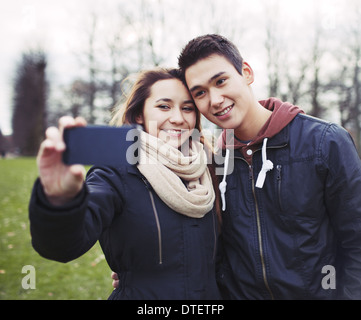 Cute young couple looking happy while taking pictures using a smart phone at the park. Mixed race teenage boy and - Stock Photo