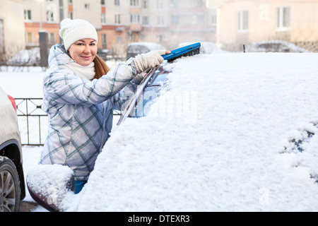 Attractive woman brushing snow from the car windshield - Stock Photo