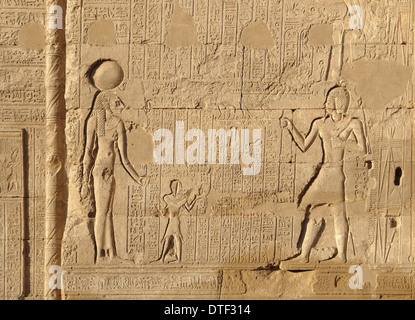 architectural detail of the historic Esana temple in Egypt (Africa) showing a stone-carved relief and lots of hieroglyphics - Stock Photo