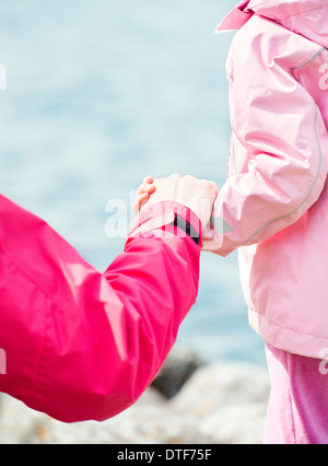 Close up of little girl and woman holding hands in nature setting - Stock Photo