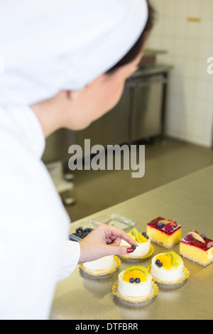 Confectioner preparing cake in bakery or confectionery - Stock Photo