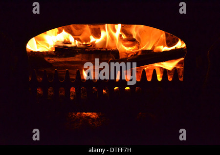 Log fire seen burning in the open grate of a woodburning stove. 'Up in flames' metaphor perhaps. - Stock Photo