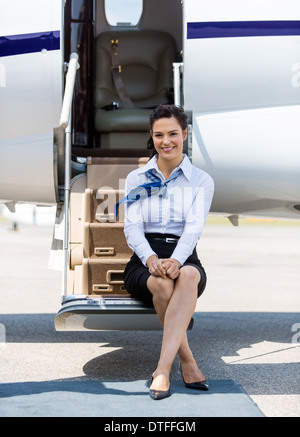 Air Hostess Sitting On Ladder Of Private Jet - Stock Photo
