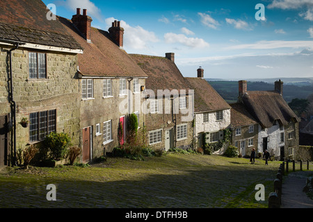 Cottages on Gold Hill, Shaftesbury in Dorset with a blue sky and white clouds. Two figures can be seen climbing - Stock Photo
