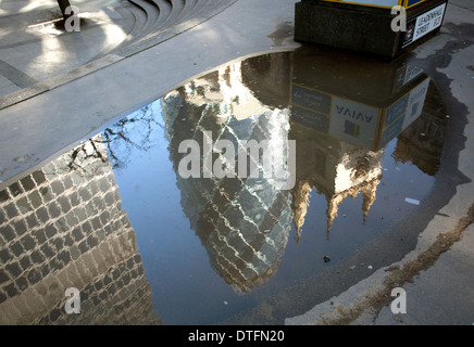 Swiss Re building ('Gherkin') reflected in puddle, City of London - Stock Photo