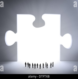 Tiny people looking and a jigsaw puzzle piece - Stock Photo