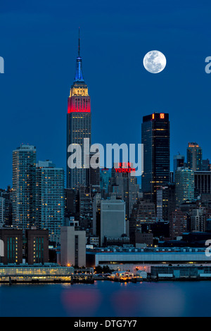 The full moon rises over the New York City (NYC) skyline during the twilight hour. A view from New Jersey across - Stock Photo