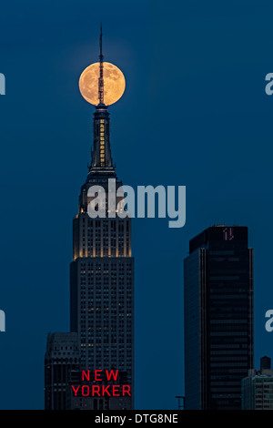 The super moon rises over the Empire State Building in New York City during the blue hour after sunset. - Stock Photo