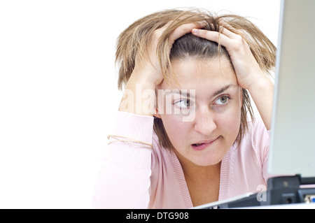 young woman sitting at the table with notebook looking stressed at her notebook holding her head (model-released) - Stock Photo