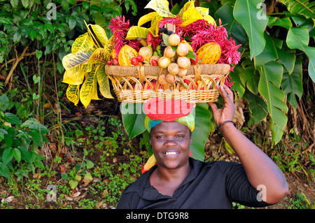 Local Grenadian woman with basket on her head near Annandale Falls. - Stock Photo