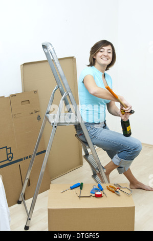 young woman sitting on a ladder opening beer bottle with a hammer (model-released) - Stock Photo