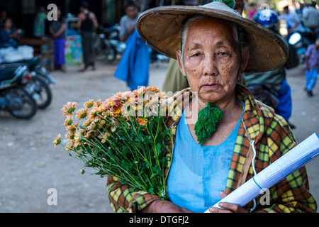 Old Burmese woman walking in the streets of Nyaung U market close to Bagan in Myanmar with some flowers. - Stock Photo