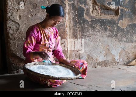 BAGAN, MYANMAR - CIRCA DECEMBER 2013: Burmese woman with a bowl full or rice - Stock Photo