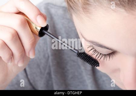 teenage girl applying mascara - Stock Photo