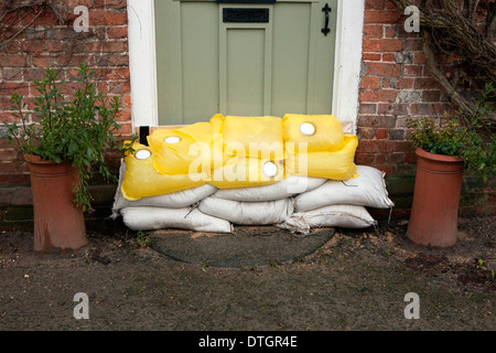 A sage green front door with sand bags, flood protection. - Stock Photo
