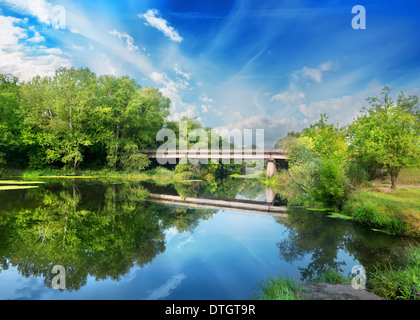 Big stone bridge over river in the forest - Stock Photo