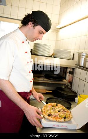Pizza baker putting a pizza in a pizza box, Upper Bavaria, Bavaria, Munich, Germany - Stock Photo