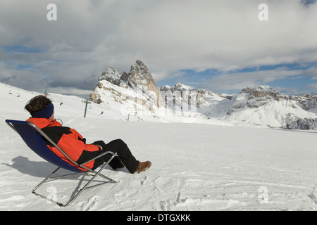 Man sitting in a deck chair on ski slope, Sella Massif, Dolomites, South Tyrol, Italy - Stock Photo