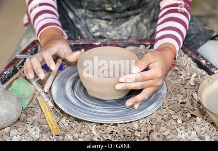 Hands molding a piece of pottery on a wheel head - Stock Photo