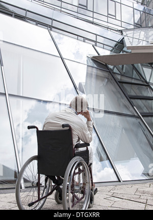 Elderly man sitting in a wheelchair in front of a modern building, Lower Saxony, Germany - Stock Photo
