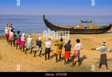 FISHERMEN HAULING SEINE NETS ON A  KERALA BEACH IN SOUTHERN INDIA - Stock Photo