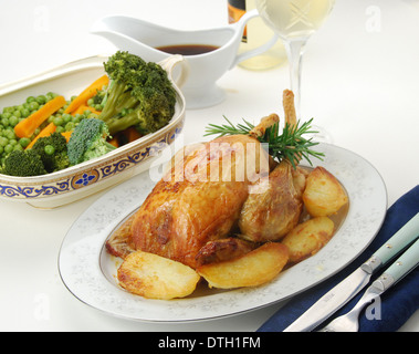 SUNDAY ROAST. Oven roast chicken with golden roast potatoes, mixed vegetables, gravy and a glass of white wine - Stock Photo