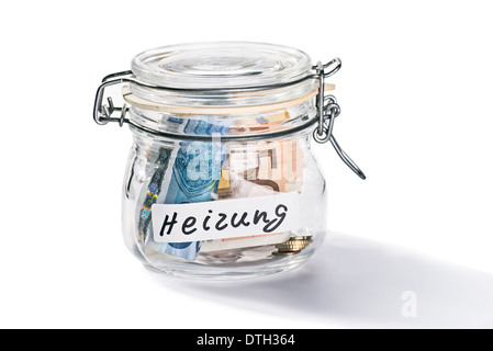 Jar with notes and coins with the inscription heating symbolizing rising heating costs. - Stock Photo