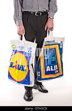 Lower body of a man in a suit, carrying plastic bags of discounters Lidl and Aldi. - Stock Photo