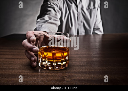 Hand of a man reaching for a glass of whiskey, which stands on a table. - Stock Photo