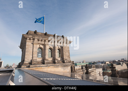 Corner tower of Reichstag Building with flying flag standing out against skyline blue sky - Stock Photo