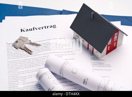 Model house, house keys and blueprints on a purchase contract for a property. - Stock Photo