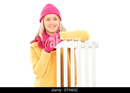 Young woman in winter clothes sitting next to a radiator - Stock Photo