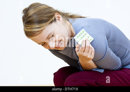 woman with strong stomach ache holding pills in her hand (model-released) - Stock Photo